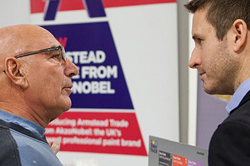 Two men speaking at a trade event